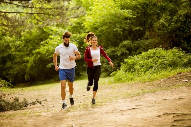 Gesunde passform und sportliche paare, die in natur laufen