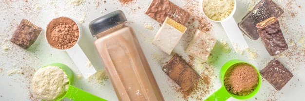 Gesunde passform und sportlicher hintergrund. abnehmen konzept. vielzahl von aromen von protein-cocktail-pulver, fertigen cocktail in der flasche und riegeln auf weißem hintergrund.