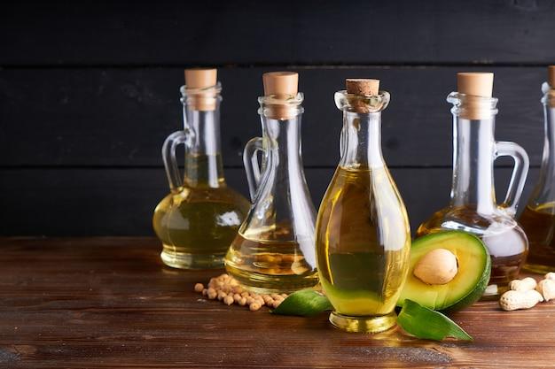 Gesunde pflanzenöle in glasflaschen. avocadoöl, kichererbsenöl, leinöl, erdnussöl, mandelöl.