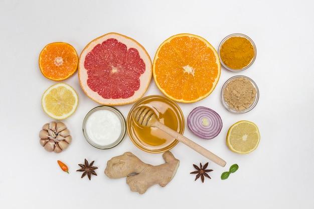 Gesunde produkte zur stärkung der immunität. zitrusfrüchte, ingwer, honig, knoblauch, zwiebeln. medizinische ernährung zu hause. flach liegen