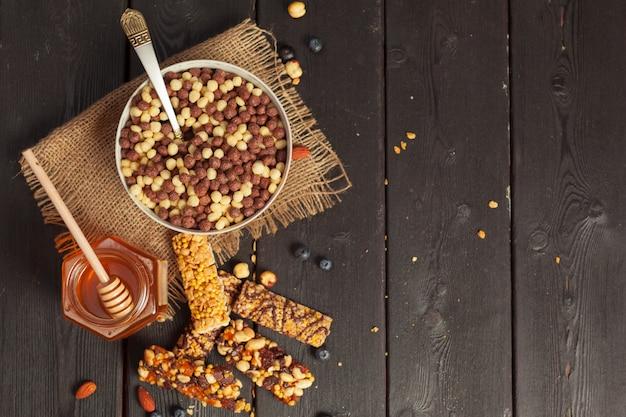 Gesunde riegel mit nüssen, samen und trockenfrüchten auf dem holztisch