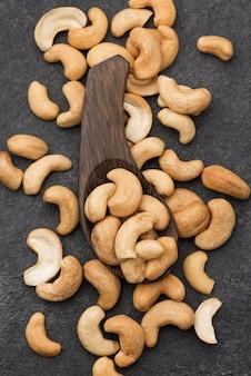 Gesunde rohe cashewnüsse und großer holzlöffel