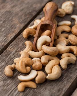 Gesunde rohe cashewnüsse und kleiner holzlöffel