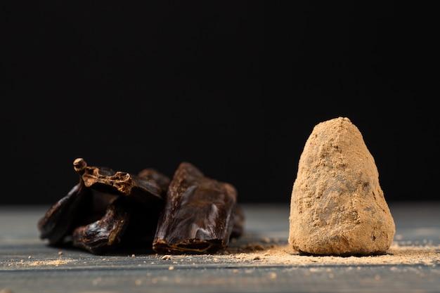 Gesunde rohe süße selbst gemachte süßigkeit des strengen vegetariers auf einem holztischhintergrund mit johannisbrotbaum