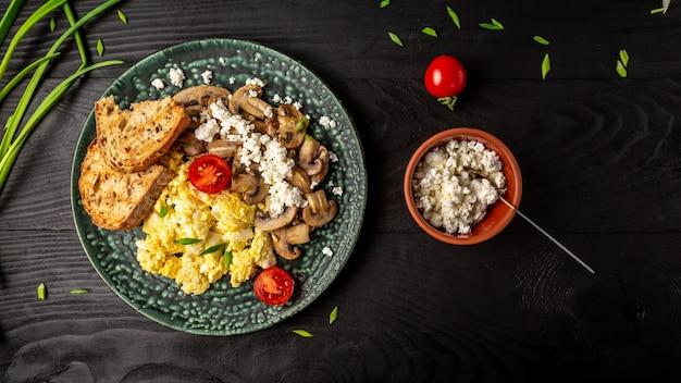 Gesunde rühreier mit pilzen, hüttenkäse und tomaten zum frühstück.