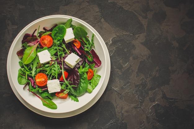 Gesunde salatblätter in einer weißen platte und in einem käse (mischungsgrüns, saftiger imbiß). essen hintergrund