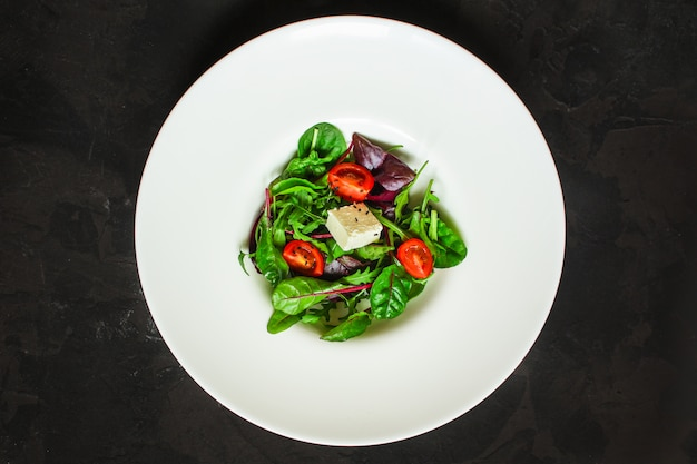 Gesunde salatblätter in einer weißen platte und in einem käse (saftiger imbiß). essen hintergrund