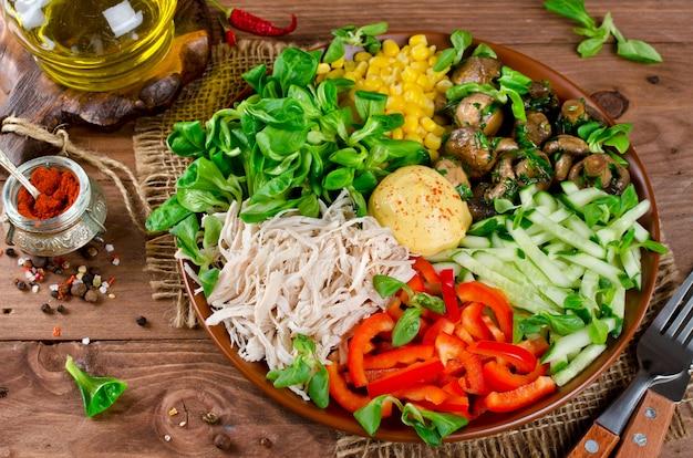 Gesunde salatschüssel mit huhn, pilzen, mais, gurken, paprika und salat mischen