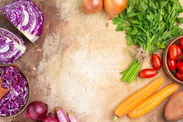 Gesunde salatzutaten von oben, hergestellt aus einem rotkohlbündel petersilie-roma-tomaten, karottenkartoffeln und zwiebeln auf einem hölzernen hintergrund mit freiem platz für text