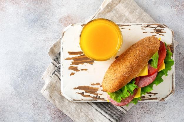 Gesunde sandwiches mit kleiebrot, grünem salat, käse, roten tomaten und geschnittener salami auf pergamentpapier und rustikalem holzständer. frühstückskonzept. ansicht von oben