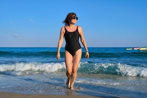 Gesunde schöne frau mittleren alters im badeanzug der sonnenbrille, der entlang der küste geht