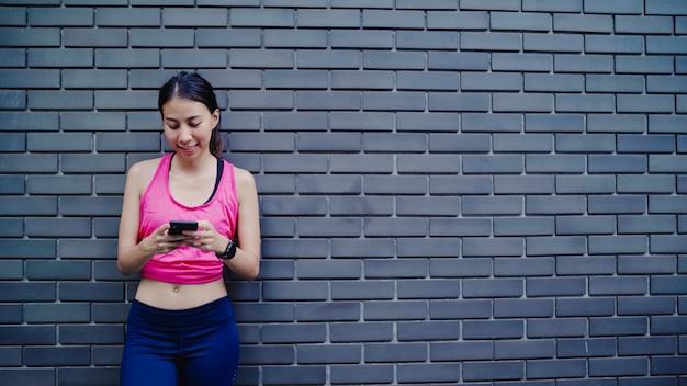 Gesunde schöne junge asiatische athletenfrau, die smartphone für die prüfung des social media verwendet