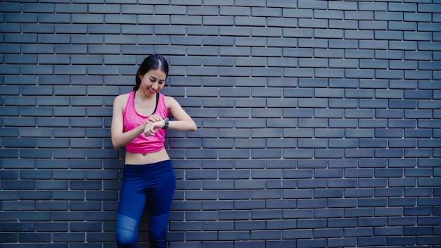 Gesunde schöne junge asiatische athletenfraueneinstellung und überprüfungsfortschritt, der herzfrequenzmonitor schaut