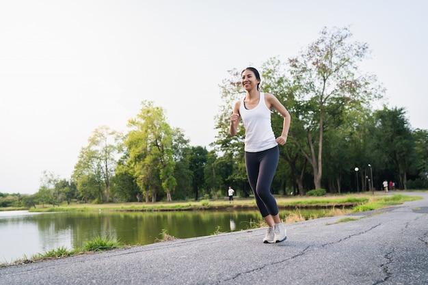 Gesunde schöne junge asiatische läuferfrau beim sportkleidungsbetrieb und -rütteln