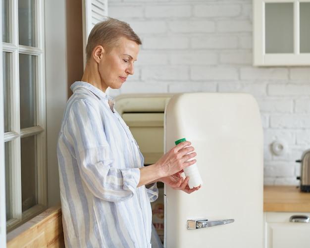 Gesunde schöne reife frau, die joghurt trinken wird, während sie in der nähe des geöffneten kühlschranks steht