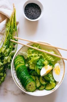 Gesunde schüssel, gurkensalat mit eiern und koriander auf marmorhintergrund, draufsicht