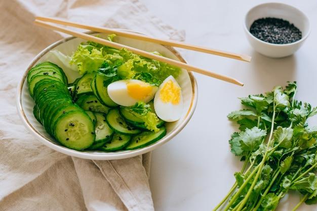 Gesunde schüssel, gurkensalat mit eiern und koriander auf marmorhintergrund