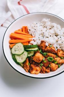 Gesunde schüssel mit hühnerfleisch, reis und gemüse in einem weißen teller auf dem tisch.
