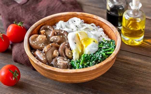 Gesunde schüssel mit reisnudeln, mariniertem shiitake, pochiertem ei und gedämpftem spinat