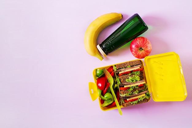 Gesunde schul-lunchbox mit rindfleischsandwich und frischem gemüse, flasche wasser und früchten auf rosa tisch. draufsicht. flach liegen