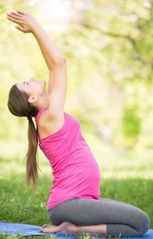 Gesunde schwangere frau, die draußen yoga in der natur tut.