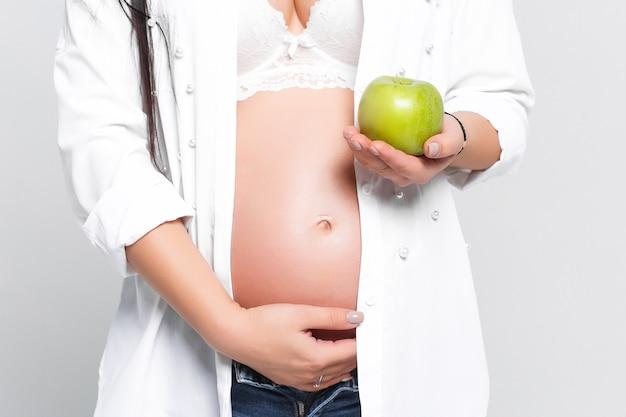 Gesunde schwangere frau mit vitaminreichem apfel, der ihren bauch hält