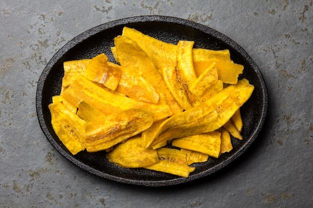 Gesunde selbst gemachte bananen-bananen-chips auf schwarzblech