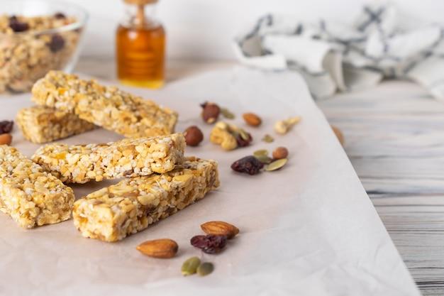 Gesunde selbst gemachte müsliriegel mit nüssen, honig und trockenfrüchten auf holztisch