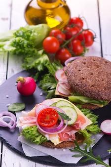 Gesunde selbst gemachte roggenburger mit frischgemüse, käse und schinken auf weißem hölzernem hintergrund.