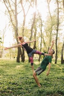 Gesunde sitzpaare, die acro yoga auf gras tun
