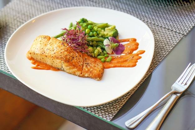 Gesunde skandinavische mahlzeit aus lachsfilet mit brokkoli, jungen bohnen und würziger roter sauce