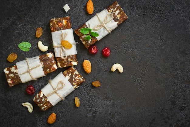 Gesunde snackbars aus getrockneten früchten und nüssen auf schwarzem betonhintergrund. draufsicht mit kopienraum