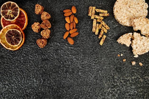 Gesunde snacks - sorte hafer müsliriegel, reiscrips, mandel, getrocknete orange