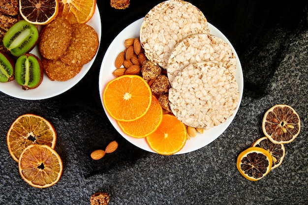 Gesunde snacks - sorte hafer müsliriegel, reiscrips, mandel, kiwi, getrocknete orange