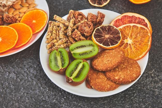 Gesunde snacks - verschiedene hafer müsliriegel, reis crips, mandeln, kiwi, getrocknete orange