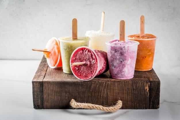 Gesunde sommerdesserts. eis am stiel. gefrorene tropische säfte, smoothies heidelbeeren. johannisbeeren, orange, mango, kiwi, banane, kokosnuss, himbeere. auf weißer marmortabelle hölzerner behälterkopienraum