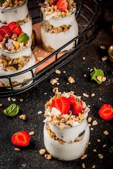 Gesunde sommerfrühstücksidee, selbst gemachter überlagerter parfe nachtisch im kleinen glas
