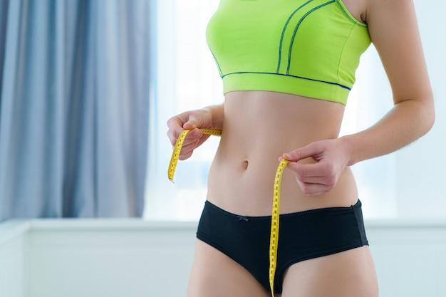 Gesunde sport fitness schlanke frau, die ihre dünne taille mit einem maßband misst, um gewichtsverlust und diätergebnisse zu zeigen. motivation und fortschritt beim abnehmen, erreichen von gewichtsverlustzielen