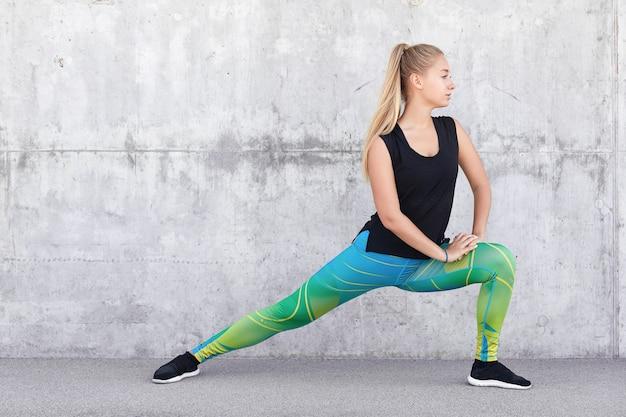 Gesunde sportlerin streckt beine trägt bedruckte leggings