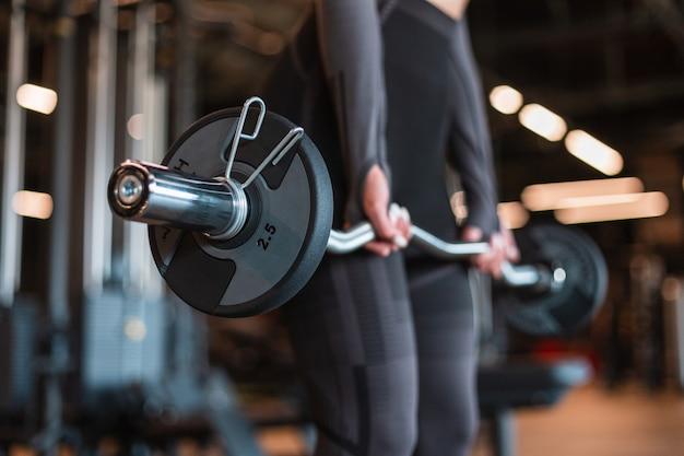 Gesunde, starke fitnesstrainerin in schwarzer sportbekleidung, die mit einer bar trainiert und trainiert und im fitnessstudio trainiert