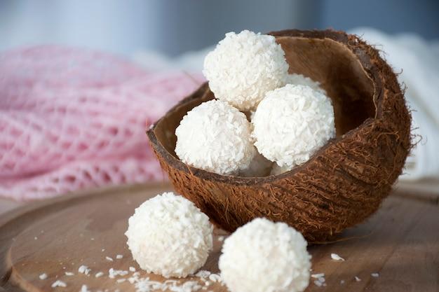 Gesunde süßigkeiten kokosnuss-glückskugeln in der nussschale auf holzbrett.
