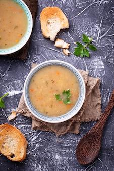 Gesunde suppe der vegetarischen erbsen auf konkretem hintergrund