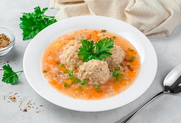Gesunde suppe mit putenfleisch frikadellen mit gemüse in einem weißen teller auf grauem hintergrund. seitenansicht, nahaufnahme.
