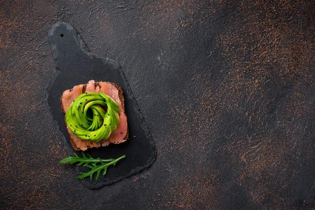Gesunde toast mit lachsen und avocado stiegen auf braunen hintergrund, draufsicht