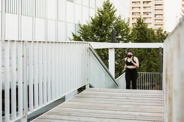 Gesunde übergewichtige junge frau, die im freien trainiert, während sie eine schützende gesichtsmaske trägt