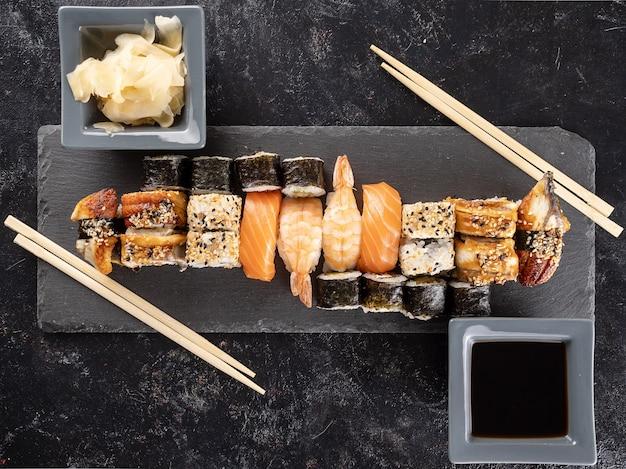 Gesunde und köstliche auswahl an sushi auf dunklem steinhintergrund. ansicht von oben