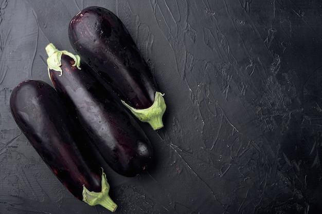 Gesunde und köstliche lila auberginen auf schwarzem stein