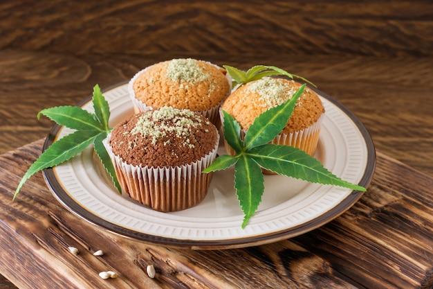 Gesunde und leckere vegane und glutenfreie muffins mit hanfsamen auf einem weißen teller auf holztisch. marihuana-cupcake-muffins mit cannabisblättern.