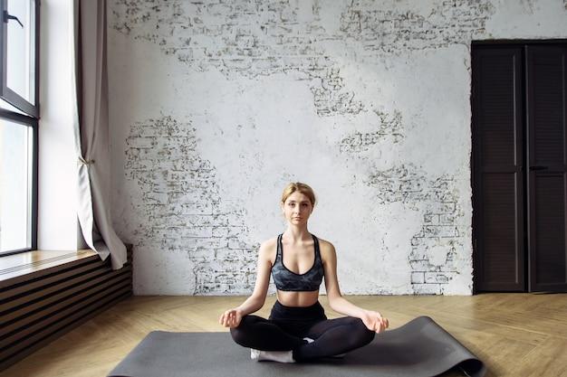 Gesunde und schöne junge frau, die zu hause in der yoga-position sitzt.