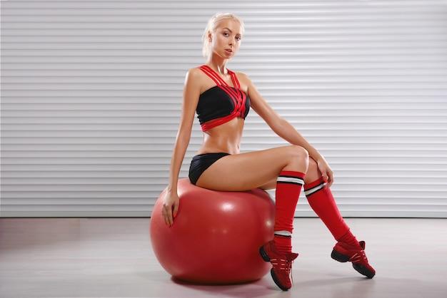 Gesunde und sportliche junge frau, die auf fitnessball am trainiert